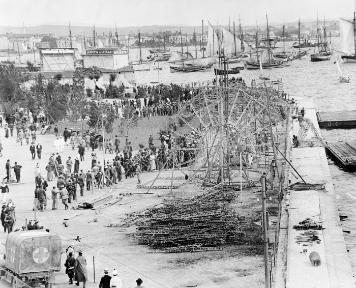 Framework of the Zeppelin LZ.85 being set up on the sea front beside the White Tower in Salonika, May 1916. ©IWM Q32030""